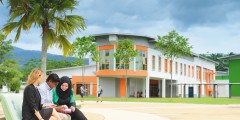 Male and female postgraduate students outside the business school, Malaysia Campus