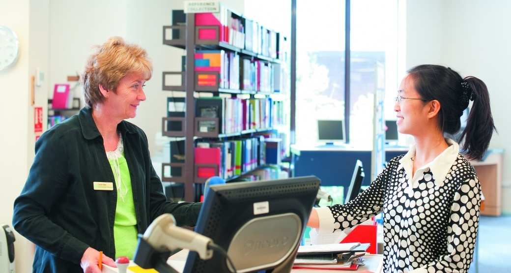 Information assistant handing books to a female undergraduate student, James Cameron-Gifford Library, Sutton Bonington campus