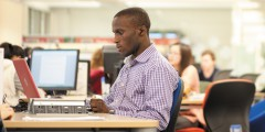 Male postgraduate student studying in Hallward Library, University Park
