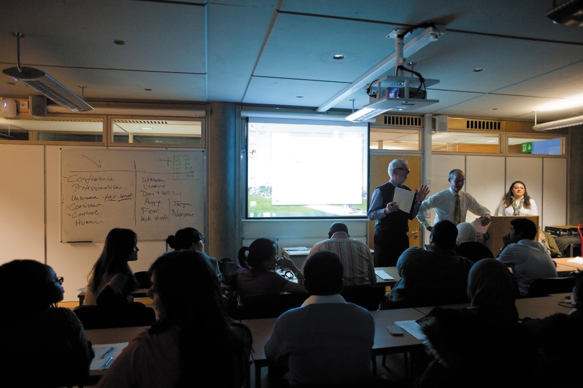 Male and female member of staff talking to students with a presentation