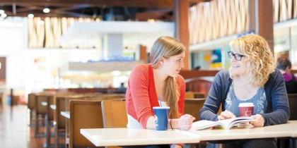 Pair of undergraduate students socialising in the Westfield Centre, Derby city centre