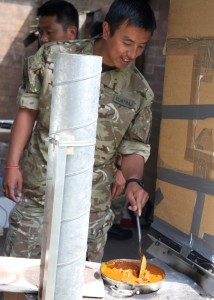 A Gurkha cooking on the Score-stove