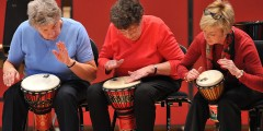 Older people taking part in a drumming workshop