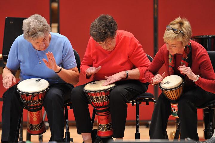 Older people taking part in a drumming workshop