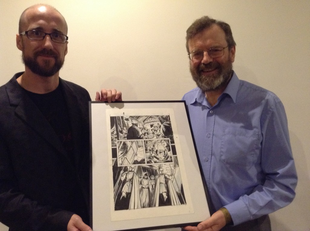 Kieron (left) and Steve with a page of the original inks from Three — art by Ryan Kelly.