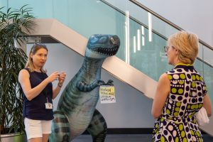 Ruth Griffin and Dame Jessica in the BiioDiscovery Institute, the image includes an inflatable dinosaur which has a social distancing message