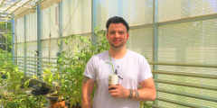 Sam Booth with a plant in the Hounsfield Facility