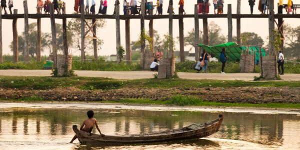 A boy in a small boat and people on a bridge in Myanmar, one of the countries where projects are eligible for GCRF funding