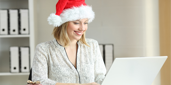 A woman managing her workload at her laptop wearing a read Christmas hat