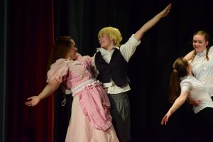 Two pantomime characters dance together, smiling widely.