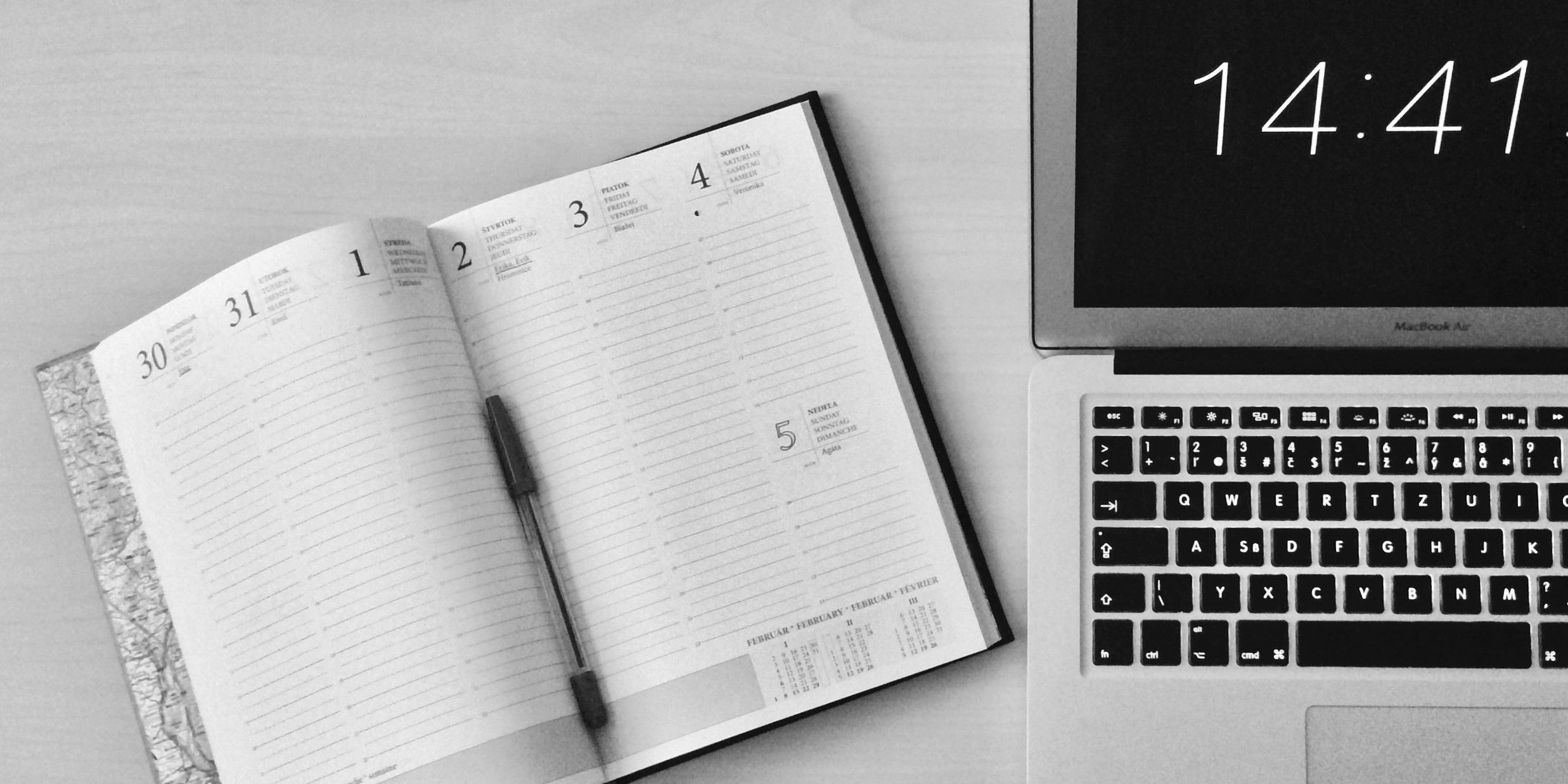 get motivated - Open laptop and open planner on a gray desk.