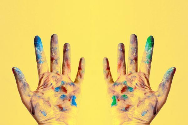creative paint-stained hands on a yellow background.