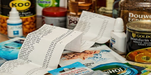 How to budget in the Kitchen - food shopping receipt surrounded by various food goods