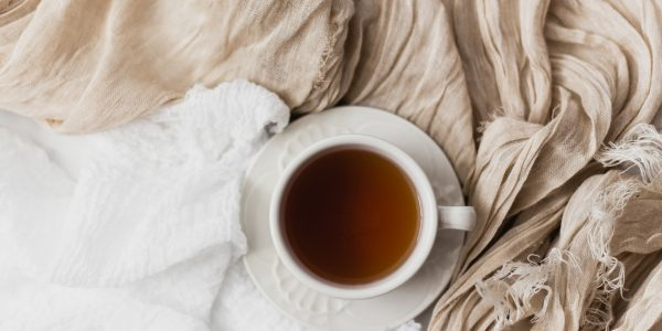 A ceramic cup and saucer of tea rest on a white bedspread