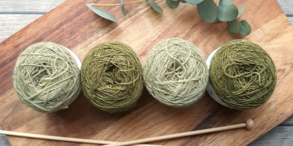 Four balls of yarn and wooden knitting needles