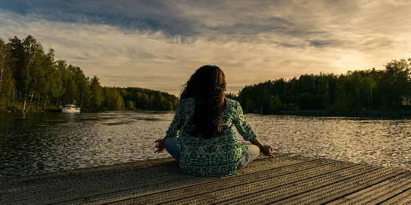 woman meditating and relaxing in front of lake