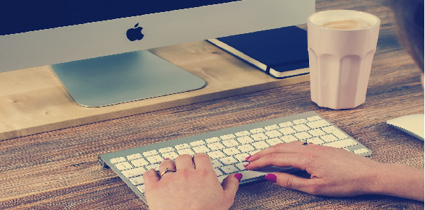 picture of hands typing on a keyboard in front of a mac computer
