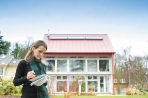 Postgraduate student outside the BASF Energy Home on Green Close, University Park