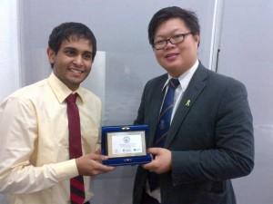 Tharaka Hettiarachchi, 2012/13 SA Diversity and Environment Officer, handing a token of appreciation to Dr Lam