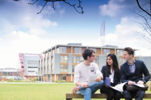 Three postgraduate students studying in front of Business School North, Jubilee campus