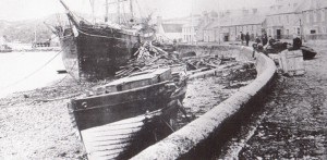 Photograph of South Beach, Stornoway after the Great Storm in October 1882 showing timber strewn on the beach, boats pushed up the beach and against the sea wall.