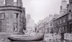 Photograph of the impact of a storm which flooded the town centre and damaged the ruined town hall.