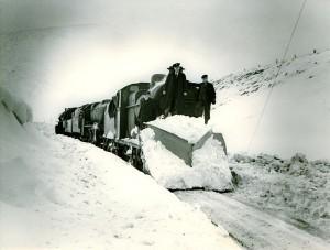 Photography of a steam locomotive and snowplough pausing just south of Riccarton Junction in the Scottish Borders. Source: Waverley Route Heritage Association Archive.