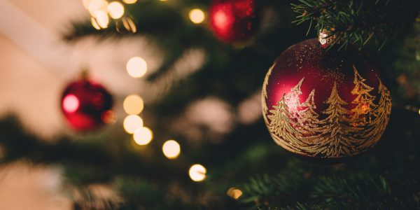 A Christmas tree decorated with red and gold baubles.