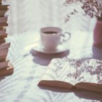 An open book on a table next to a pile of books, a cup of tea and a plant.
