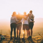 A group of four friends hugging on a mountain.