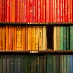 A shelf of books that are all colour coordinated, creating a gradient from red to yellow to green.