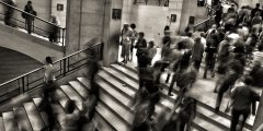 A blurred image of people walking up a steps.