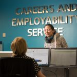 A woman standing talks to a woman sitting behind a desk with a computer. Careers and Employability Service is on the wall in the background.