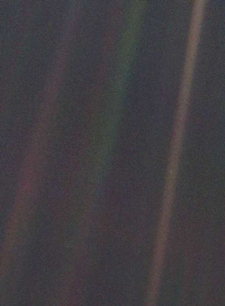 An image of the earth taken by Voyager 1. Due to Voyager's distance, the earth is just a tiny white dot in the centre of one of three scattered rays of light.