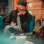 Man wearing headphones sits in a coffee shop writing on a notepad.