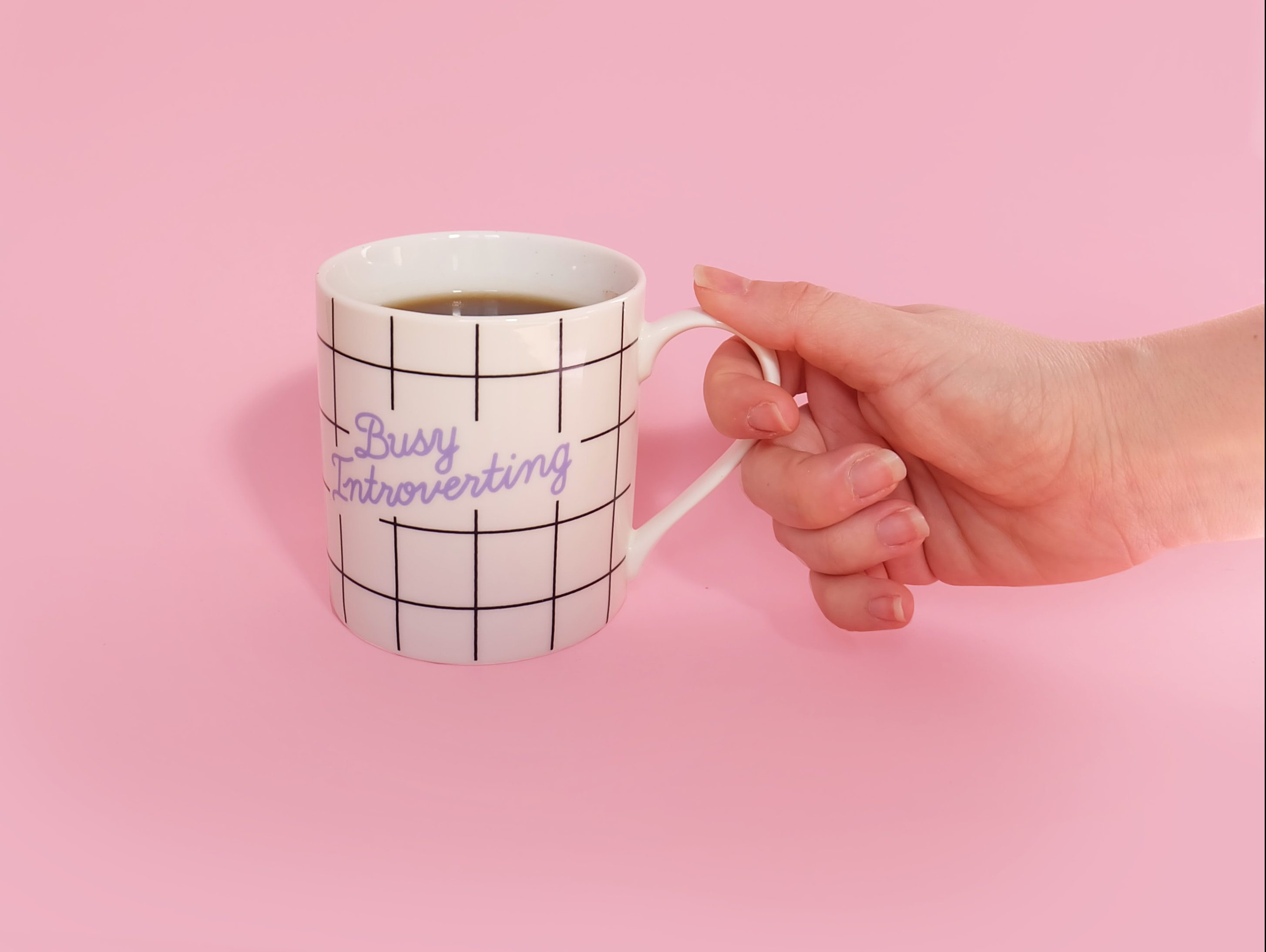 A hand holding a mug that reads 'busy introverting'.