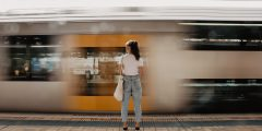 Woman stands on a platform in front of fast moving train.