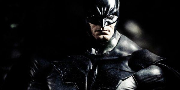 Batman standing alone in shadow.