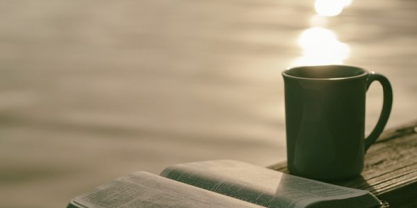 A cup and an open book sit on a flat outside surface.