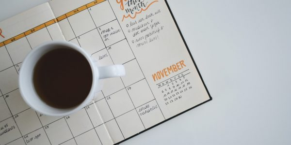 A mug of coffee sitting on top a planner.
